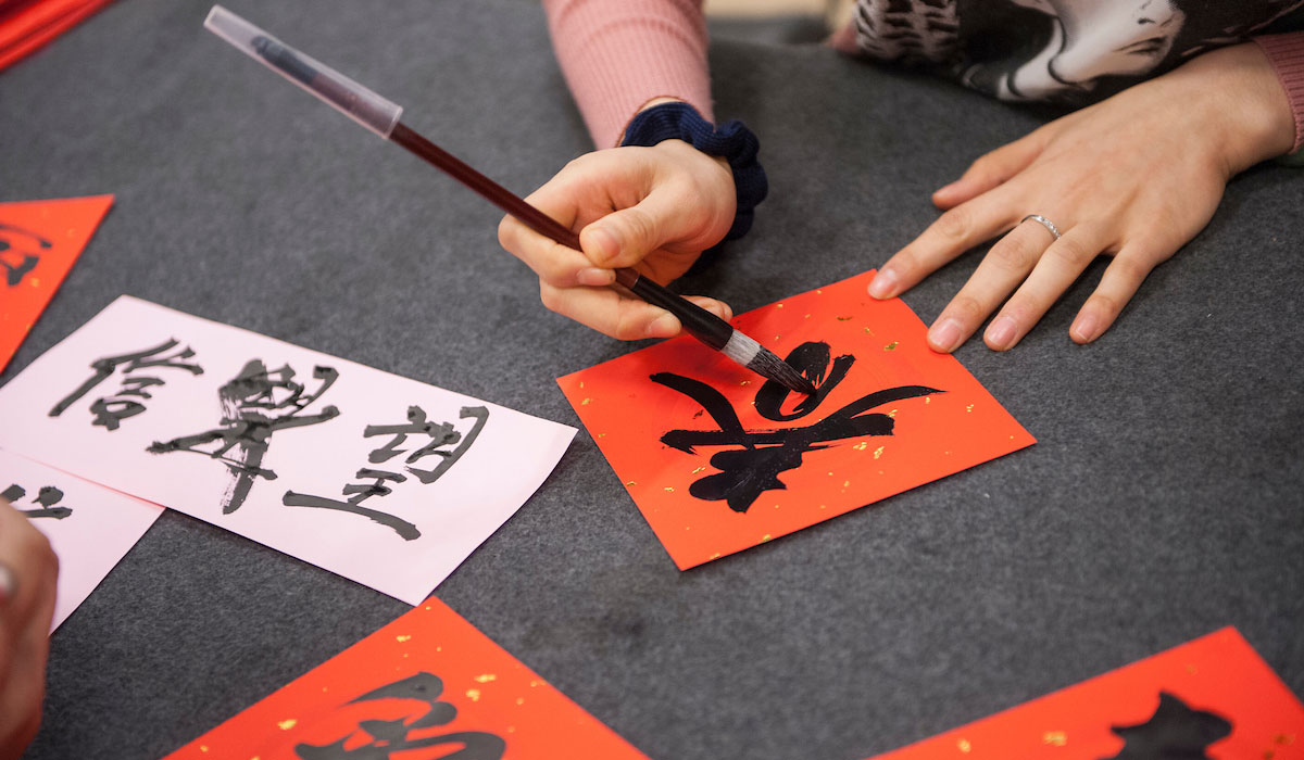 Hands writing Chinese characters
